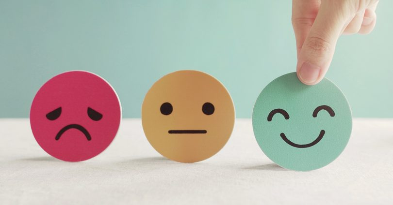 A sad face, neutral face and happy face.