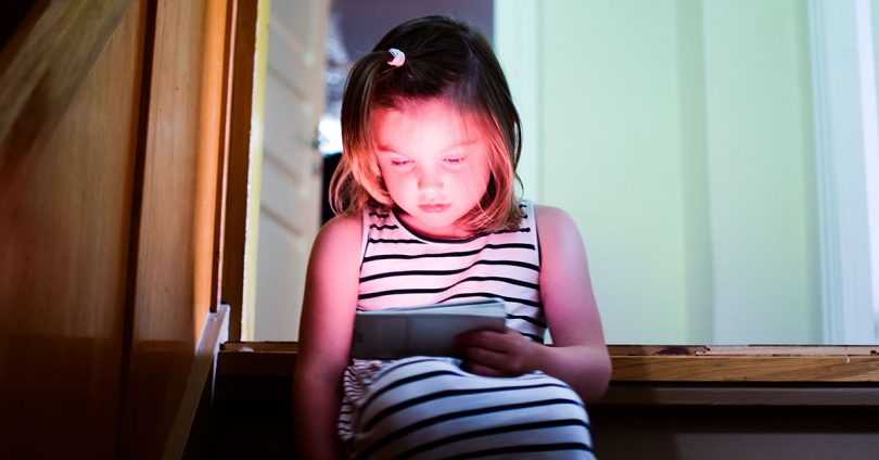 A child sitting on the stairs in the house and looking at the screens of the tablet PC, smartphone.
