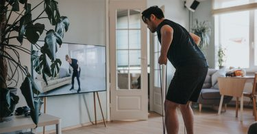 man doing home workout with resistance band