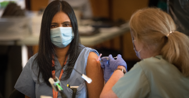 health-care worker gets their COVID-19 vaccine