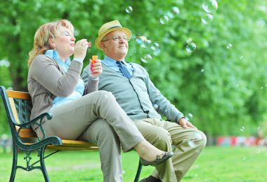 two seniors on a bench blowing bubbles
