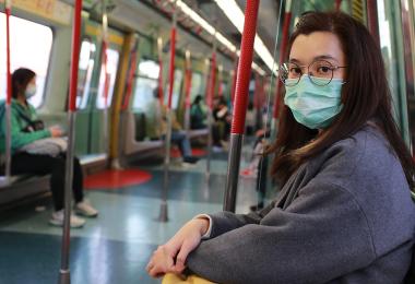 Woman wearing mask on public transit looking anxious