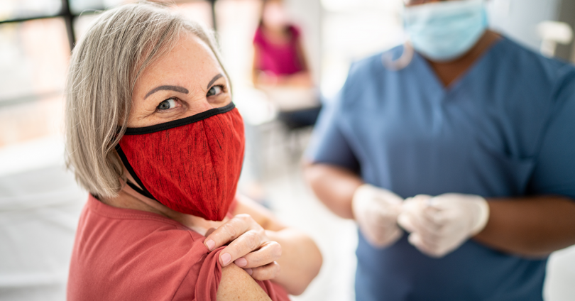 woman rolls up her sleeve to get vaccine