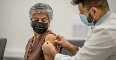 A doctor sticks a band-aid on the arm of a woman who got her shot.