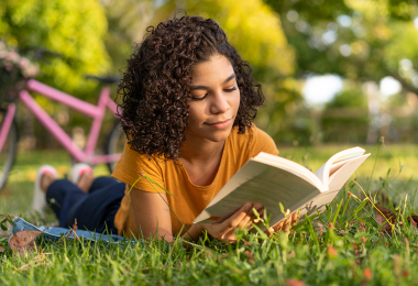 Youth reading a book outside