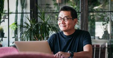 Man wearing glasses using computer